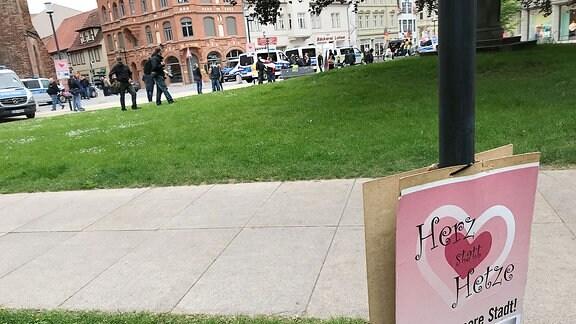 Plakat Herz statt Hetze, im Hintergrund eine Demo und Polizei.