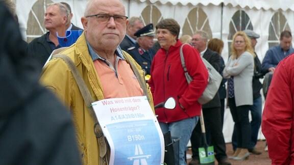 """Ein Befürworter der sogenannten Hosenträgervariante mit einem Schild um den Hals: """"Was wird mit dem Hosenträger? A14/A39/B190n"""""""