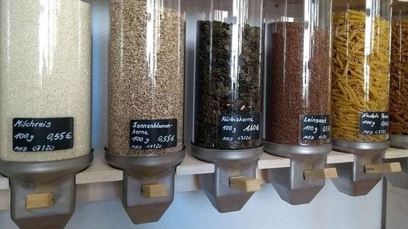 Reis, Körner und Nudeln in großen Spendern an der Wand.