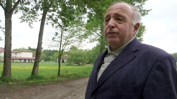 Mann steht vor einem Grundstück mit Wiese, Haus und Bäumen.