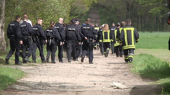 Polizei sucht Waldgebiet ab.