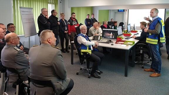 Menschen in Uniform und Schutzwesten sitzen bei einer Präsentation zusammen