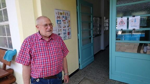 Mann steht vor geöffneter Tür.
