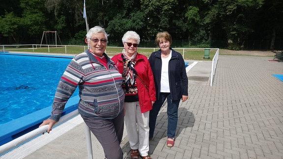 Drei ältere Frauen stehen an Rand eines Schwimmbeckens.