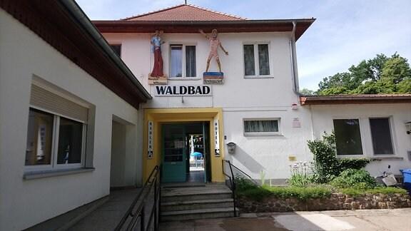 """Haus mit Schild """"Eingang Waldbad""""."""