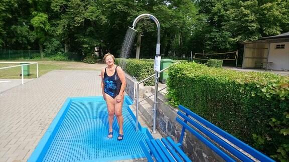 Frau duscht sich in Freibad ab.