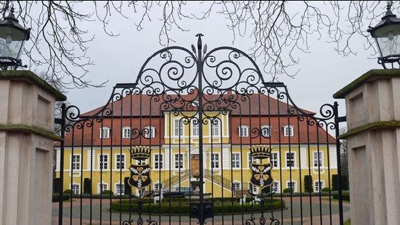 Schloss mit gelbem Anstrich durch einen Zaun fotografiert