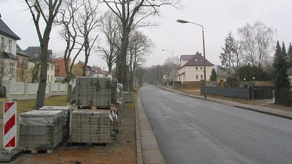Eine Straße mit daneben abgelagertem Baumaterial.