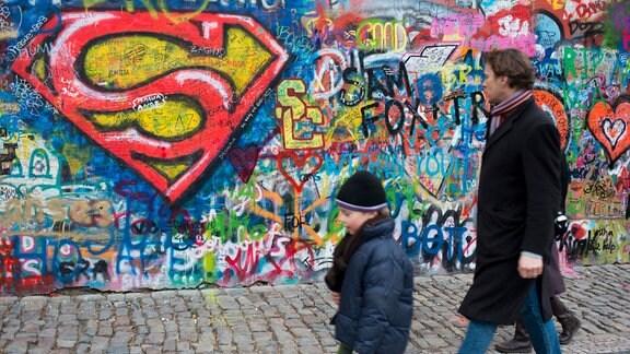 Mann und Kinder laufen an Wand mit Superman-Graffito vorbei