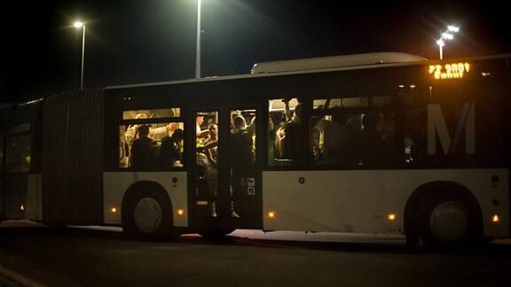 Mehrere Menschen stehen dicht gedrängt in einem Bus auf einem Rollfelld bei Nacht