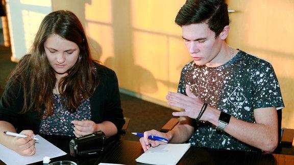 Eine junge Frau und ein junger Mann sitzen an einem Tisch  und diskutieren, auf dem Tisch liegen mehrere Blätter Papier und eine Videokamera.