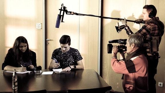 Zwei junge Erwachsene sitzen an einem Tisch und schreiben etwas auf Papier, sie werden von zwei weiteren Menschen per Videokamera gefilmt.
