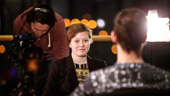 Zu sehen ist eine junge Frau, die auf einen jungen Mann schaut, dessen Hinterkopf zu sehen ist.