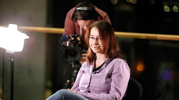 Eine junge Frau sitzt auf einem Stuhl, im Hintergrund ist ein Kameramann zu sehen.