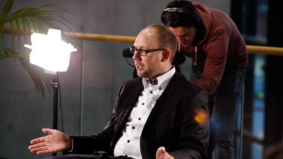 Ein junger Mann sitzt gestikulierend in einem schwarzen Sessel, im Hintergrund ist ein Kameramann zu sehen.