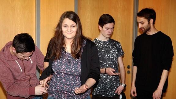 Zu sehen sind vier Menschen aus einem Fernsehproduktionsteam. Die einzige Frau auf dem Bild schaut in die Kamera.