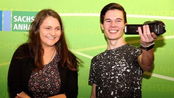 Zwei junge Erwachsene stehen lächelnd vor einer grünen Wand, der junge Mann hält eine Videokamera in die Hand.