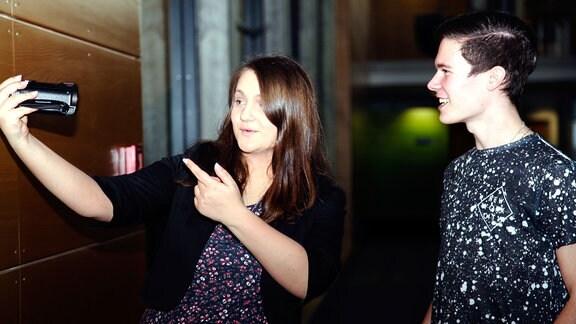 Zwei junge Erwachsene stehen nebeneinander und filmen sich selbst mit einer Videokamera.