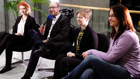 Vier Menschen sitzen nebeneinander auf schwarzen Stühlen, einer von ihnen ist männlich und hält ein Mikrofon in der Hand.