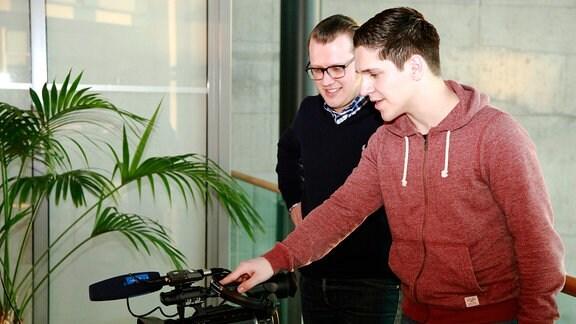 Zwei junge Männer blicken auf eine Videokamera, die im Bild steht.