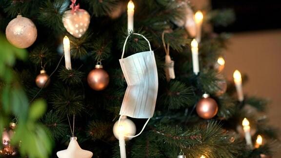 Am Weihnachstbaum hängt ein Mund-Nasen-Schutz