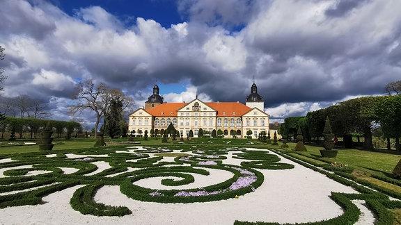 Schloss Hundisburg bei wolkigem Himmel mit Gartenanlage im Vordergrund
