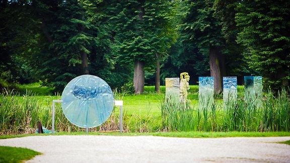 Blick auf einen Park, ind em blau, gelb und grün eingefärbte Objekte stehen