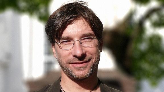 Ein Mann mit Brille und dunklen Haaren schaut in die Kamera