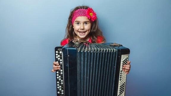 Ein Mädchen mit einem Akkordeon.