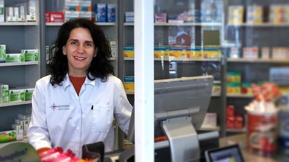 Eine Apothekerin am Thresen in Ihrem Geschäft