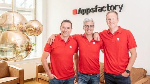 Drei Männer stehen vor dem Logo Appsfactory