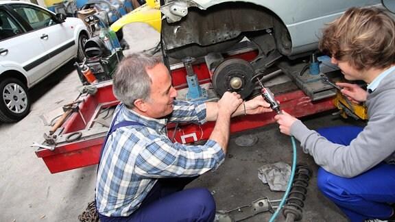 Teenager mit älterem Automechaniker in einer Werkstatt