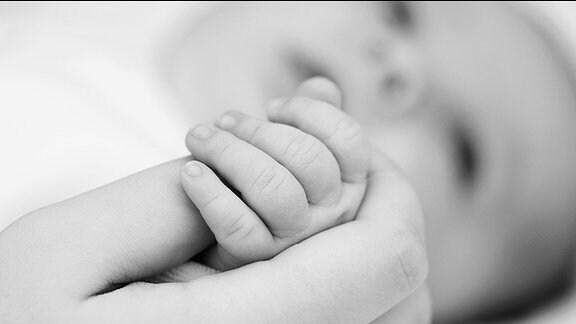 Eine Frau hält die Hand eines Neugeborenen