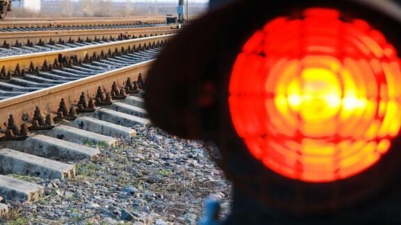 An einer Bahnstrecke leuchtet ein rotes Haltesignal auf.