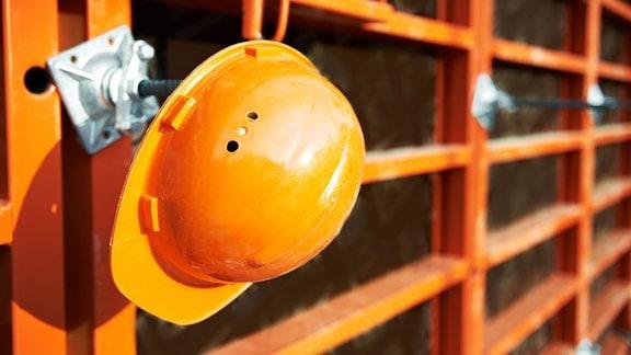 Ein Helm hängt an einem Gerüst.