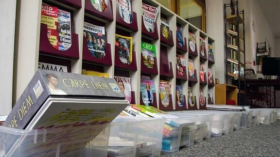 Regale mit Zeitschriften und Büchern in Plasteboxen.