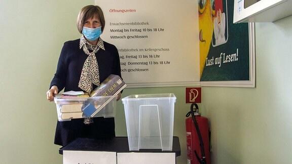 Eine Frau steht neben zwei Ausleih- bzw Rückgabeboxen.