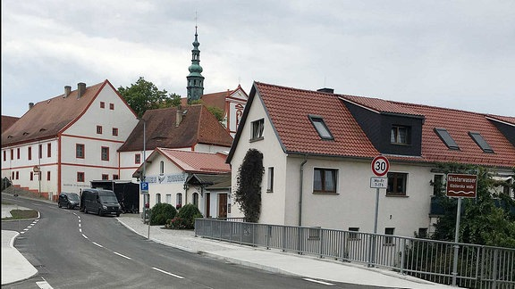 Eine frisch sanierte Straße mit einer Brücke kurz vor der Eröffnung.