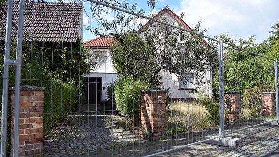 Haus hinter Absperrzaun
