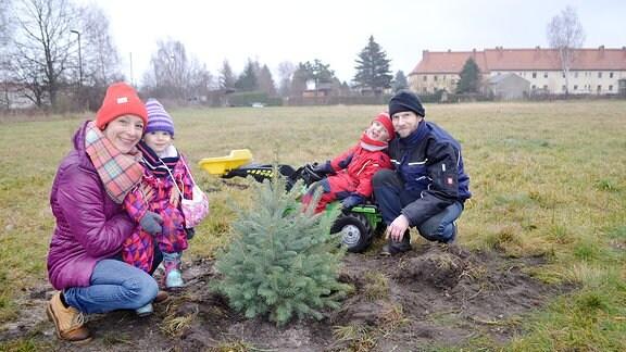 Ein Paar mit kleinen Kindern hockt neben einem frisch gepflanztem Baum.