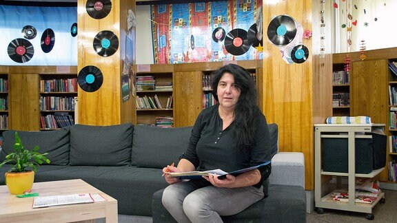 Eine Fraus sitzt in der Bibliothek im Planetarium Hoyerswerda, blättert in einem Buch und schaut zur Kamera.