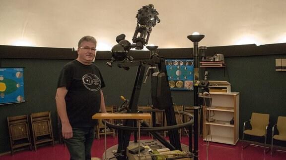 Ein Mann steht neben dem Projektor im Planetarium Hoyerswerda und schaut zur Kamera.