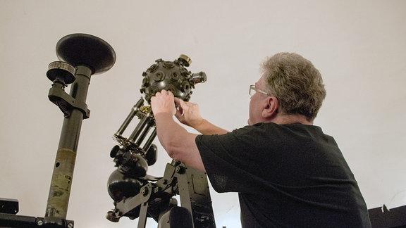 Ein Mann justiert etwas am Projektor des Planetariums Hoyerswerda.