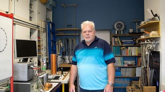 Ein Mann steht in einer Werkstatt im Planetarium Hoyerswerda und schaut zur Kamera.