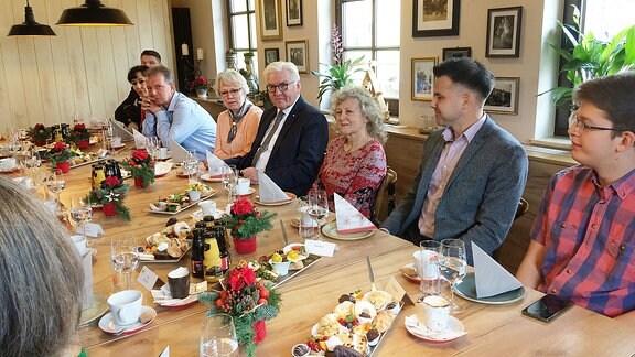 Bundespräsident Steinmeier sitzt in Pulsnitz mit Menschen an einer Kaffeetafel.