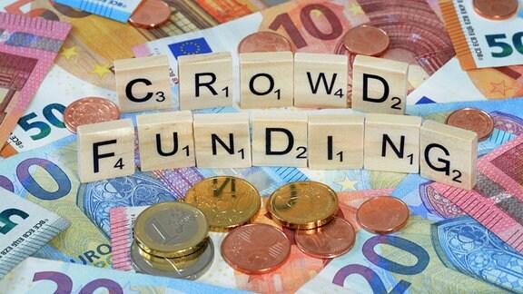 Hoilzblöcke mit Buchstaben bilden den Begriff Crowdfunding.Darunter liegen Geldscheine und Münzen.