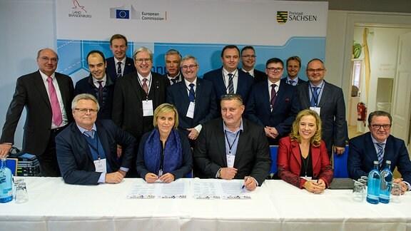Hinter einem Konferenztisch stehen und sitzen Vertreter von 14 europäischen Kohleregionen