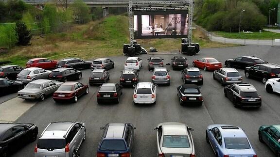 Auf einem Parkplatz stehen Autos vor einer Kino-Leinwand