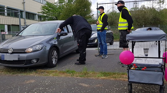 Männer mit Mundschutzmasken kontrollieren an der Einfahrt eines Autokinos ein Fahrzeug