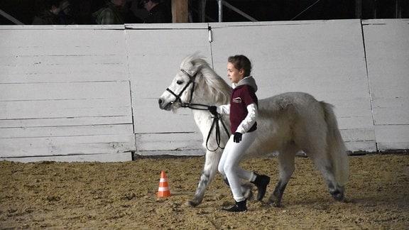 Mädchen rennt mit Pony in der Reithalle.